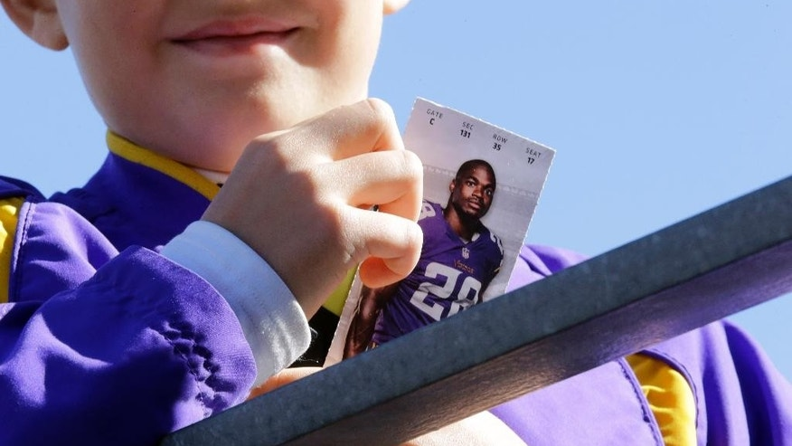 A young boy holds a ticket featuring a photo of Minnesota Vikings running back Adrian Peterson before the start of an NFL football game between the Minnesota Vikings and the New England Patriots, Sunday, Sept. 14, 2014, in Minneapolis. Peterson was indicted in Texas on Friday for using a branch to spank one of his sons. He turned himself in early Saturday at a jail in Montgomery County, was processed and released, and deactivated by the Vikings for Sunday's game. (AP Photo/Ann Heisenfelt)