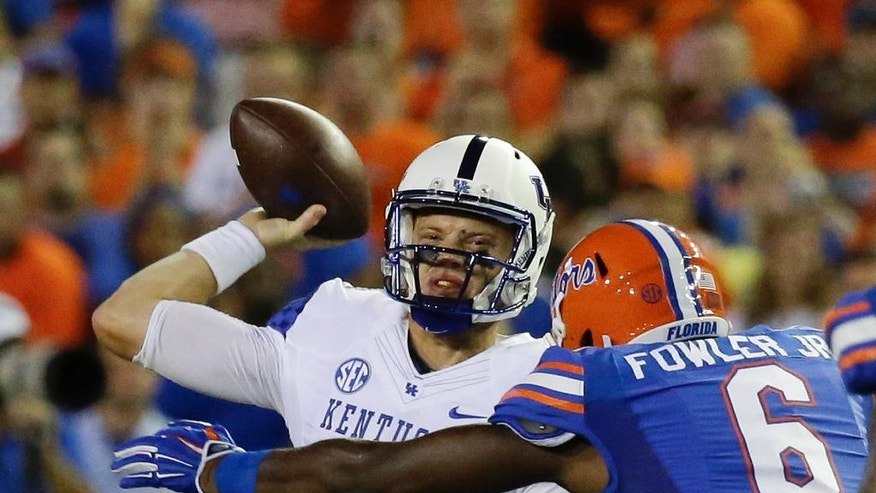 Kentucky quarterback Patrick Towles (14) gets off a pass just before he is hit by Florida defensive lineman Dante Fowler Jr. (6) during the first half of an NCAA college football game in Gainesville, Fla., Saturday, Sept. 13, 2014. (AP Photo/John Raoux)