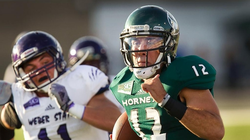 Sacramento State quarterback Garrett Safron (12) runs away from Weber State defender Billy Green (11) for a touchdown during the first half of an NCAA college football game in Sacramento, Calif., on Saturday, Sept. 13, 2014.(AP Photo/Steve Yeater)