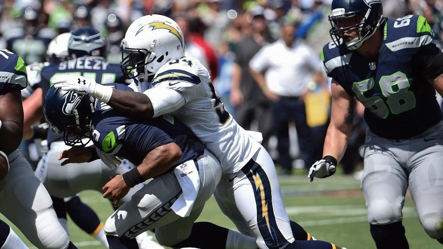 Seattle Seahawks quarterback Russell Wilson, left, fumbles as he is sacked by San Diego Chargers outside linebacker Melvin Ingram during the first half of an NFL football game on Sunday, Sept. 14, 2014, in San Diego. The Seahawks recovered the fumble. (AP Photo/Denis Poroy)