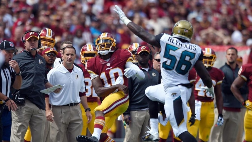 Washington Redskins quarterback Robert Griffin III (10) throws and injures his left ankle in front of Jacksonville Jaguars outside linebacker LaRoy Reynolds (56) during the first half of an NFL football game Sunday, Sept. 14, 2014, in Landover, Md. The Redskins have said he will not return to the game. (AP Photo/Nick Wass)