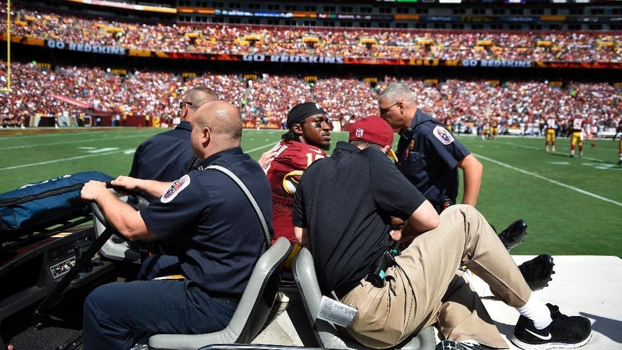 Washington Redskins quarterback Robert Griffin III (10) leaves an NFL football game on a cart after injuring his left ankle during the first half against the Jacksonville Jaguars, Sunday, Sept. 14, 2014, in Landover, Md. (AP Photo/Nick Wass)