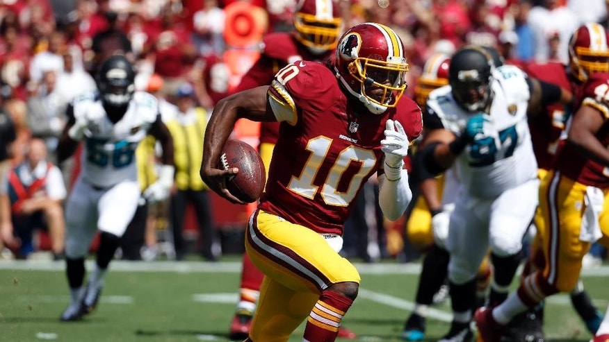Washington Redskins quarterback Robert Griffin III (10) runs with the ball during the first half of an NFL football game against the Jacksonville Jaguars, Sunday, Sept. 14, 2014, in Landover, Md. (AP Photo/Alex Brandon)