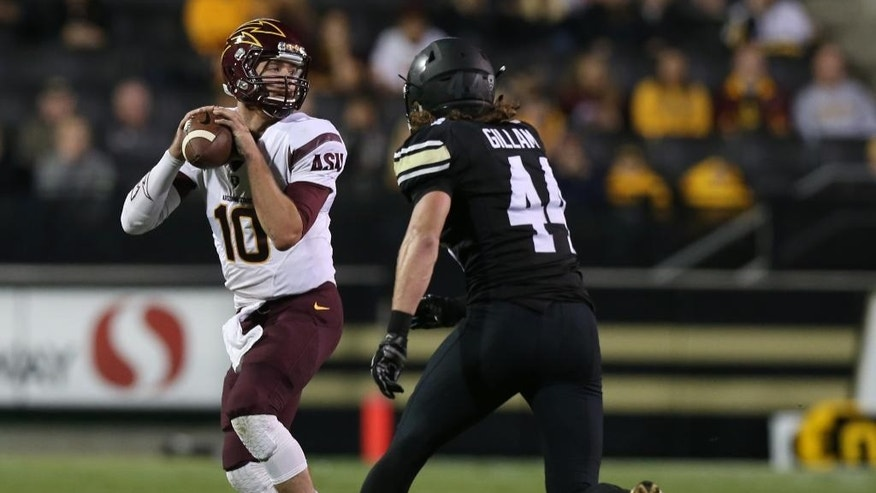 Arizona State quarterback Taylor Kelly, left, looks to pass under pressure from Colorado linebacker Addison Gillam in the first quarter of an NCAA college football game in Boulder, Colo., on Saturday, Sept. 13, 2014. (AP Photo/David Zalubowski)