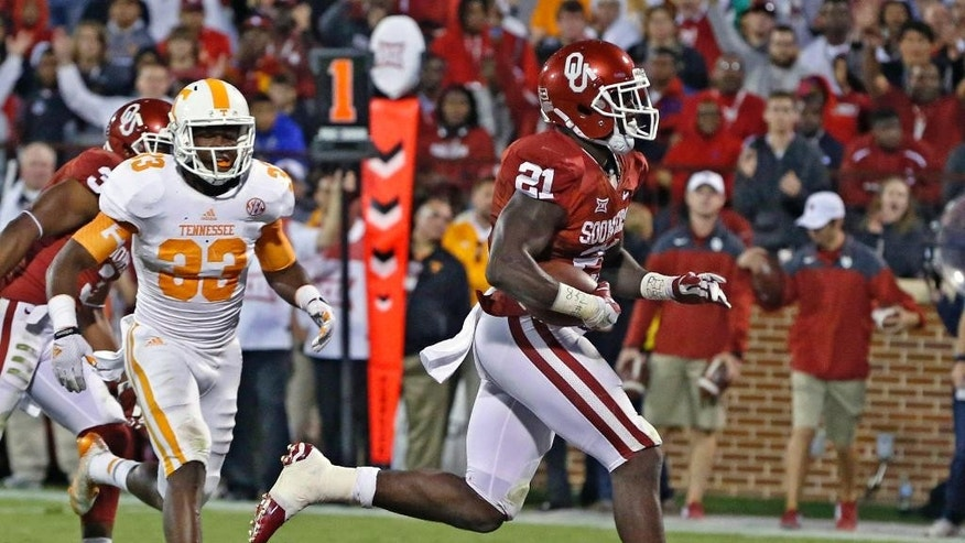 Oklahoma running back Keith Ford (21) runs into the end zone for a touchdown in front of Tennessee defensive back LaDarrell McNeil (33) in the second quarter of an NCAA college football game in Norman, Okla., Saturday, Sept. 13, 2014. (AP Photo/Sue Ogrocki)