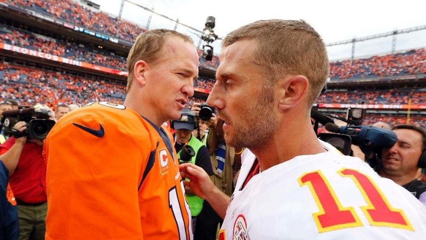 Denver Broncos quarterback Peyton Manning (18) greets Kansas City Chiefs quarterback Alex Smith after an NFL football game, Sunday, Sept. 14, 2014, in Denver. The Broncos won 24-17. (AP Photo/Jack Dempsey)