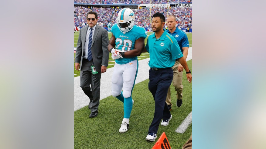 Miami Dolphins running back Knowshon Moreno (28) walks off the field after an injury during the first half of an NFL football game against the Buffalo Bills, Sunday, Sept. 14, 2014, in Orchard Park, N.Y. (AP Photo/Bill Wippert)