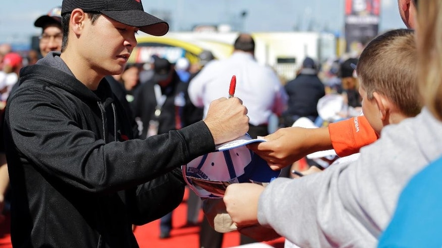 CORRECTS NAME OF EVENT AND SLUG - Kyle Larson (42) autographs for fans as he arrives at the tent for driver/crew chiefs meeting before NASCAR Sprint Cup Series MyAFibStory.com 400 race at Chicagoland Speedway in Joliet, Ill., Sunday, Sept. 14, 2014. (AP Photo/Nam Y. Huh)