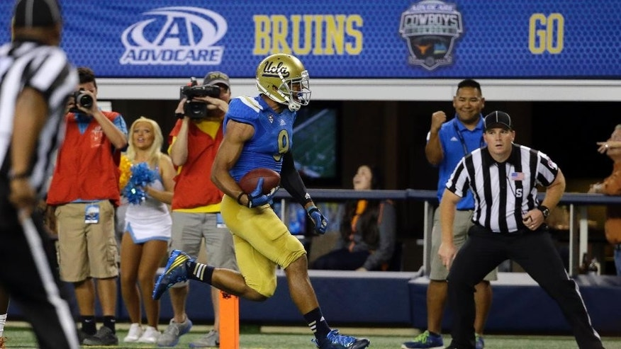UCLA wide receiver Jordan Payton (9) scores a touchdown in the final minutes against Texas in an NCAA college football game, Saturday, Sept. 13,  2014, in Arlington, Texas. UCLA won 20-17. (AP Photo/Tony Gutierrez)
