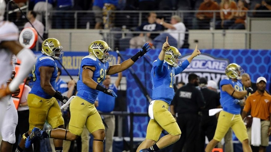 UCLA quarterback Jerry Neuheisel (11), Matt Dickerson (99) and Malcolm Bunche (78) celebrate after UCLA scored a touchdown against Texas in the final minutes of an NCAA college football game, Saturday, Sept. 13,  2014, in Arlington, Texas. UCLA won 20-17. (AP Photo/Tony Gutierrez)