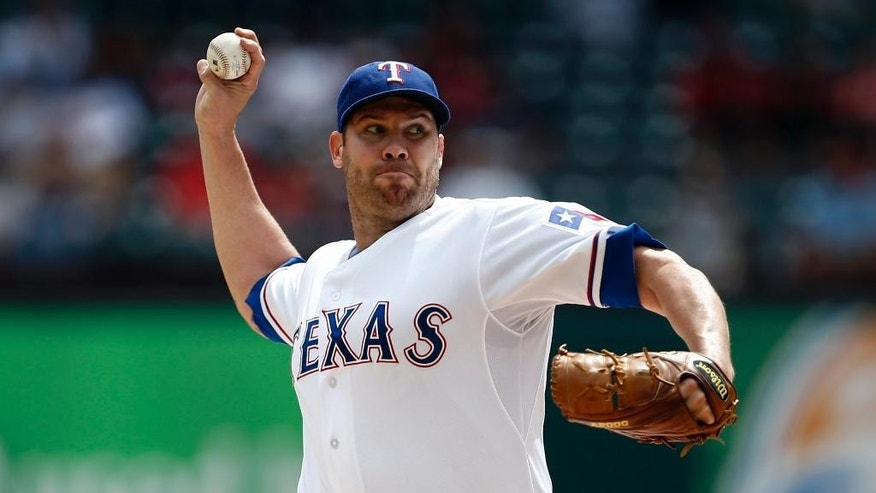 Texas Rangers starting pitcher Colby Lewis delivers to the Atlanta Braves during the first inning of a baseball game, Sunday, Sept. 14, 2014, in Arlington, Texas. (AP Photo/Jim Cowsert)