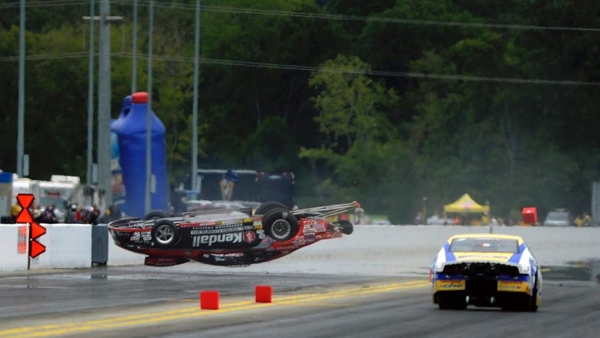 In this photo provided by the NHRA, Vieri Gaines goes airborne during a first-round victory over Allen Johnson in Pro Stock at the Pep Boys NHRA drag races Sunday, Sept. 14, 2014, at zMAX Dragway in Concord, N.C. Gaines was not injured in the incident. (AP Photo/NHRA, Marc Gewertz)