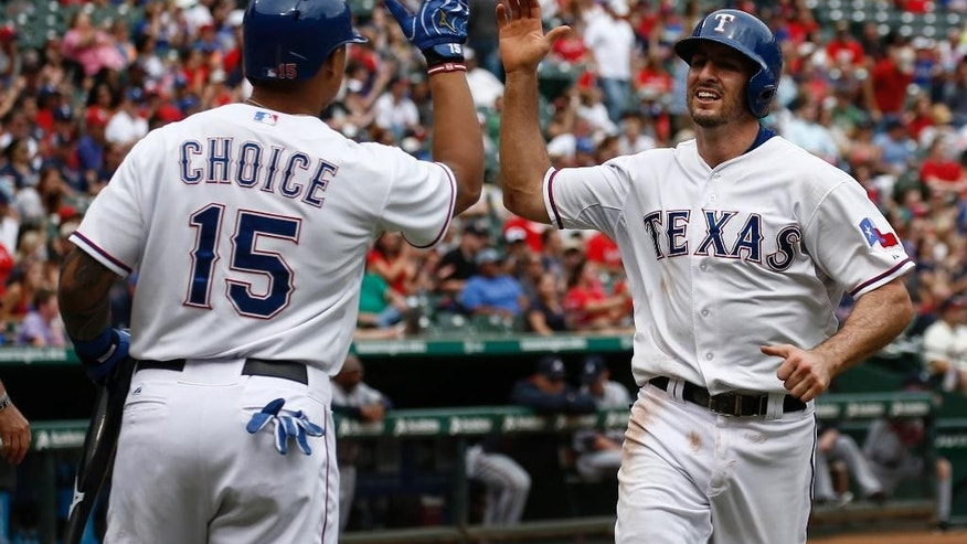 Texas Rangers' Adam Rosales, right, is congratulated by Michael Choice after scoring on a hit by Luis Sardinas against the Atlanta Braves during the second inning of a baseball game, Sunday, Sept. 14, 2014, in Arlington, Texas. (AP Photo/Jim Cowsert)