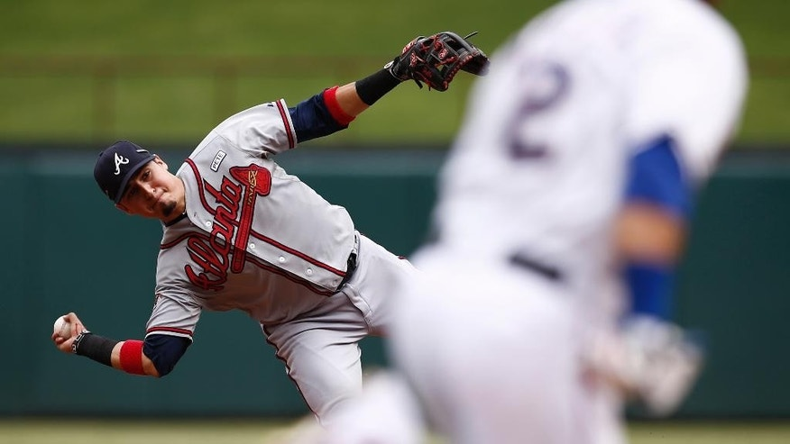 Atlanta Braves second baseman Ramiro Pena throws late to first on a single by Texas Rangers' Leonys Martin during the fourth inning of a baseball game, Sunday, Sept. 14, 2014, in Arlington, Texas. (AP Photo/Jim Cowsert)