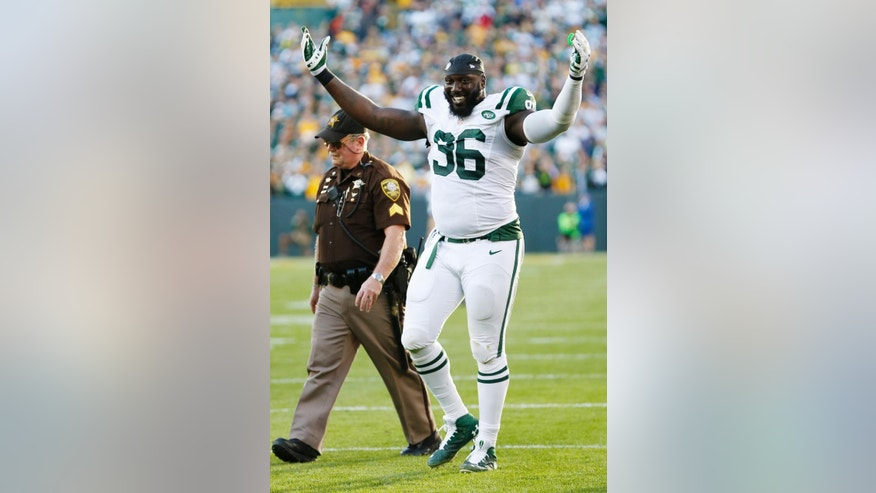 New York Jets' Muhammad Wilkerson reacts as he walks off the field after being ejected from the game after a fight during the second half of an NFL football game against the Green Bay Packers Sunday, Sept. 14, 2014, in Green Bay, Wis. (AP Photo/Tom Lynn)