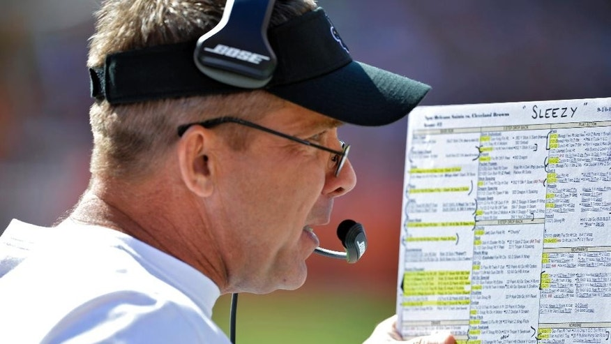 New Orleans Saints coach Sean Payton looks over his play sheet on the sideline in the third quarter of an NFL football game against the Cleveland Browns on Sunday, Sept. 14, 2014, in Cleveland. (AP Photo/David Richard)