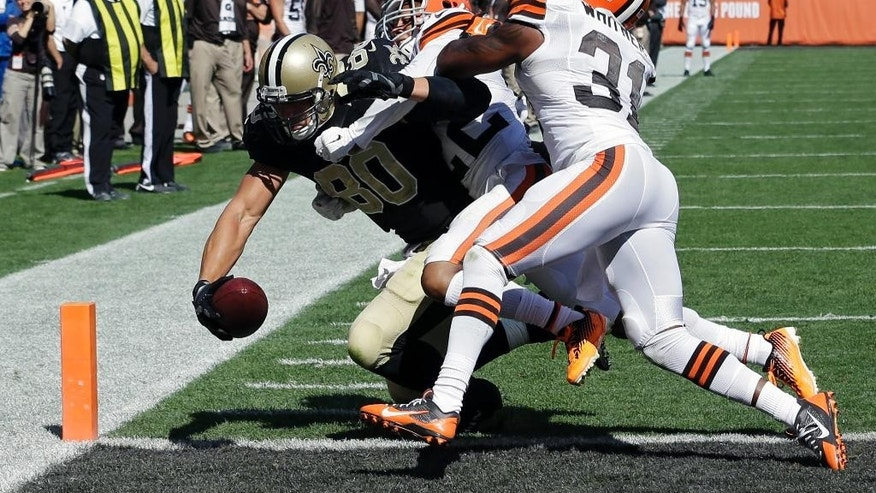 New Orleans Saints tight end Jimmy Graham (80) scores on a 1-yard touchdown pass against Cleveland Browns cornerback Buster Skrine (22) and strong safety Donte Whitner (31) in the third quarter of an NFL football game Sunday, Sept. 14, 2014, in Cleveland. (AP Photo/Tony Dejak)
