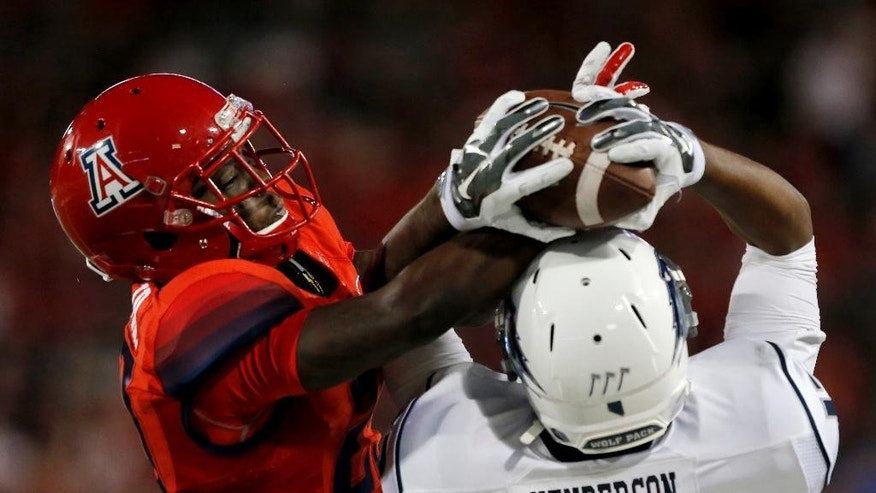 Arizona cornerback Jarvis McCall Jr. (29) and Nevada wide receiver Hasaan Henderson (12) battle for the ball during the first half of the NCAA college football game, Saturday, Sept. 13, 2014, in Tucson, Ariz. (AP Photo/Rick Scuteri)