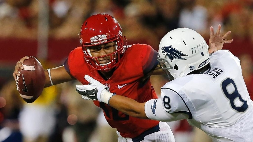 Nevada defensive end Ian Seau (8) pressures Arizona quarterback Anu Solomon (12) during the first half of the NCAA college football game, Saturday, Sept. 13, 2014, in Tucson, Ariz. (AP Photo/Rick Scuteri)