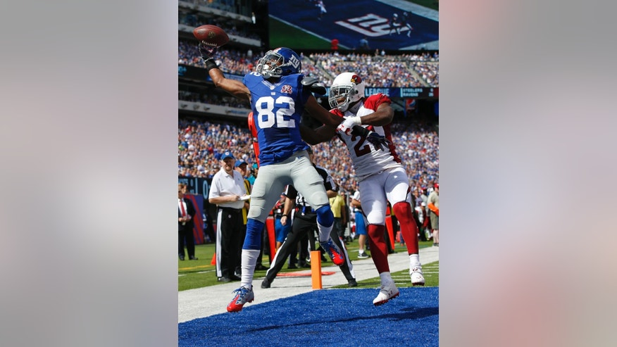 New York Giants wide receiver Rueben Randle (82) catches a pass for a touchdown in front of Arizona Cardinals' Patrick Peterson (21) during the first half of an NFL football game Sunday, Sept. 14, 2014, in East Rutherford, N.J. (AP Photo/Kathy Willens)