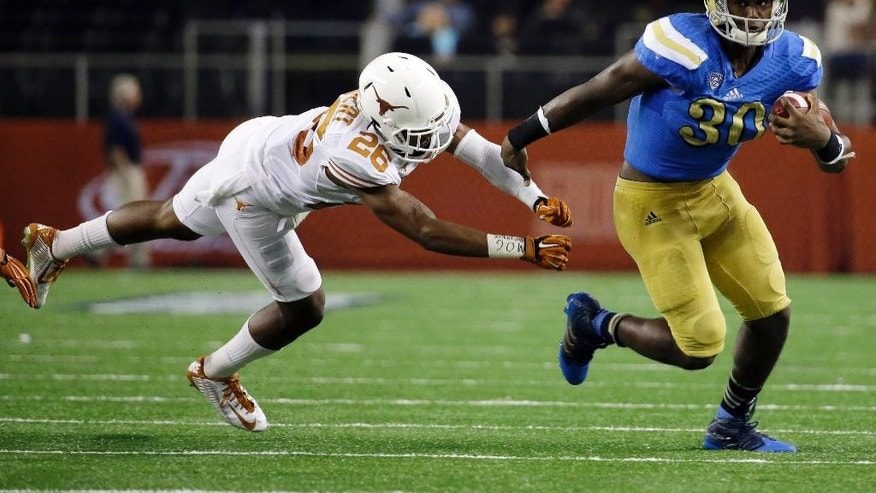 UCLA's Myles Jack (30) eludes Texas safety Adrian Colbert (26) during the second half of an NCAA college football game, Saturday, Sept. 13, 2014, in Arlington, Texas. (AP Photo/Tony Gutierrez)