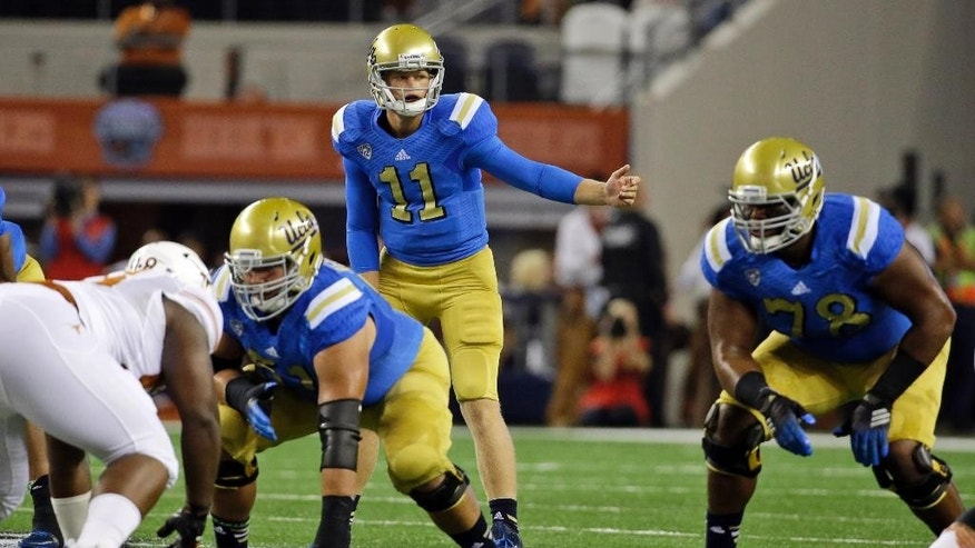 UCLA quarterback Jerry Neuheisel (11) calls a play against Texas during the first half of an NCAA college football game, Saturday, Sept. 13, 2014, in Arlington, Texas. (AP Photo/Tony Gutierrez)