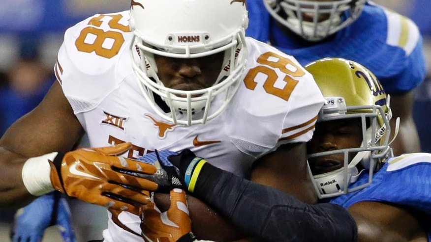 Texas running back Malcolm Brown (28) is tackled by UCLA defensive back Ishmael Adams during the first half of an NCAA college football game, Saturday, Sept. 13,  2014, in Arlington, Texas. (AP Photo/Tony Gutierrez)