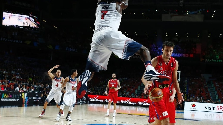 United States' Kenneth Faried, centre, dunks during the final World Basketball match between the United States and Serbia at the Palacio de los Deportes stadium in Madrid, Spain, Sunday, Sept. 14, 2014. (AP Photo/Andres Kudacki)