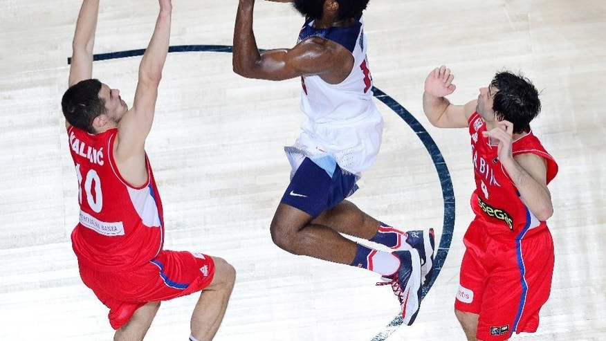 United States' James Harden throws the ball against Serbia's Nikola Kalinic, left, and Serbia's Milos Teodosic during the final World Basketball match between the United States and Serbia at the Palacio de los Deportes stadium in Madrid, Spain, Sunday, Sept. 14, 2014. (AP Photo/Manu Fernandez)