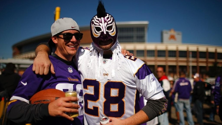 Two fans tailgate outside TCF Bank Stadium wearing Adrian Peterson jerseys before the start of an NFL football game between the Minnesota Vikings and the New England Patriots, Sunday, Sept. 14, 2014, in Minneapolis. Peterson was indicted in Texas on Friday for using a branch to spank one of his sons. He turned himself in early Saturday at a jail in Montgomery County, was processed and released, and deactivated by the Vikings for Sunday's game.  (AP Photo/The Star Tribune, Jeff Wheeler)  MANDATORY CREDIT; ST. PAUL PIONEER PRESS OUT; MAGS OUT; TWIN CITIES LOCAL TELEVISION OUT