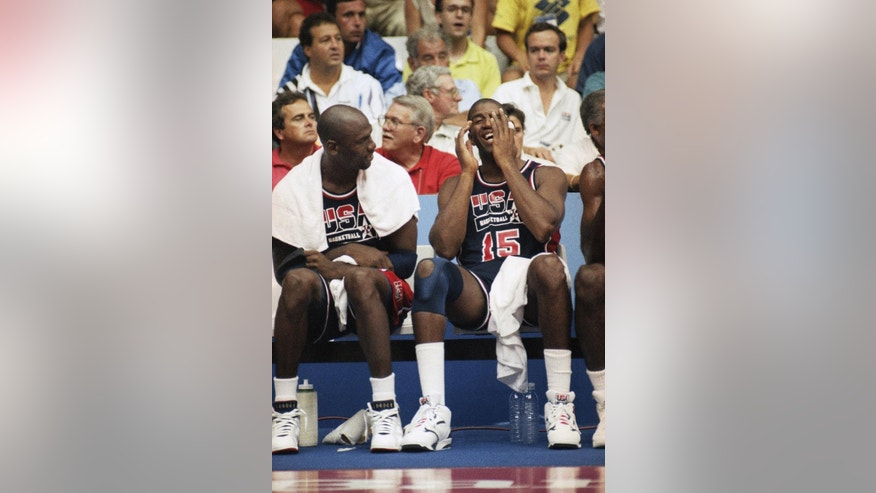 "FILE - In this Aug. 4, 1992, file photo, Earvin ""Magic"" Johnson, right, laughs as he sits with Michael Jordan during a basketball game against Puerto Rico in Barcelona, Spain. (AP Photo/Susan Ragan, File)"