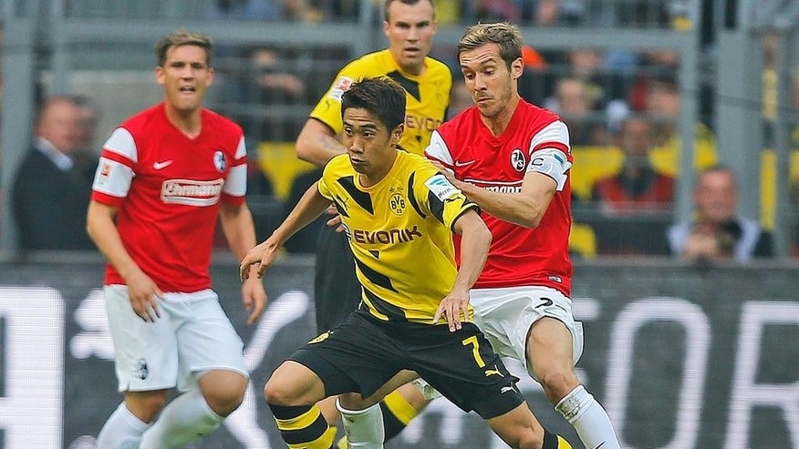 Dortmund's Shinji Kagawa from Japan, front, and Freiburg's Pavel Krmas from Czech Republic, right, challenge for the ball during the German first division Bundesliga soccer match between BvB Borussia Dortmund  and SC Freiburg in Dortmund, Germany, Saturday, Sept. 13, 2014. (AP Photo/Frank Augstein)