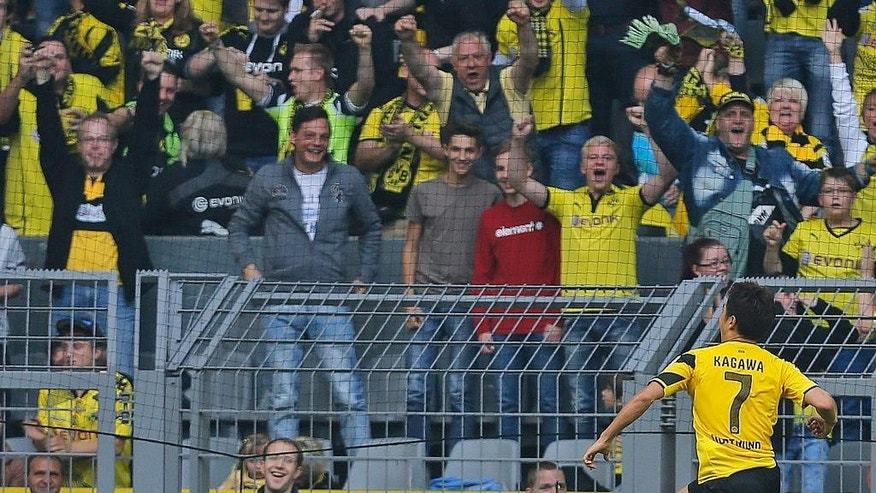 Dortmund's Shinji Kagawa from Japan, right, celebrates after scoring during the German first division Bundesliga soccer match between BvB Borussia Dortmund  and SC Freiburg in Dortmund, Germany, Saturday, Sept. 13, 2014. (AP Photo/Frank Augstein)