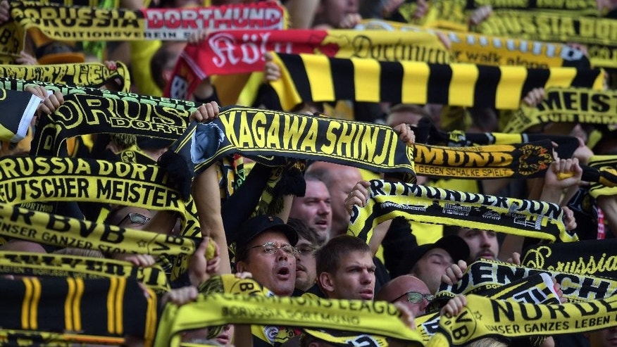 A fan holds up a scarf  reading 'Kagawa Shinji' during the German Bundesliga soccer match between Borussia Dortmund and SC Freiburg at in Dortmund, Germany,  Saturday Sept. 13, 2014. (AP Photo/dpa,Federico Gambarini)