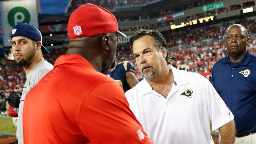 St. Louis Rams head coach Jeff Fisher, second from right, shakes hands with Tampa Bay Buccaneers head coach Lovie Smith after the Rams defeated the Bucs 19-17 during an NFL football game Sunday, Sept. 14, 2014, in Tampa, Fla. (AP Photo/Brian Blanco)