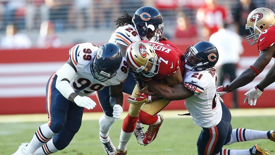 San Francisco 49ers quarterback Colin Kaepernick (7) is tackled by Chicago Bears defensive end Lamarr Houston (99), cornerback Tim Jennings (26) and free safety Ryan Mundy (21) during the first quarter of an NFL football game in Santa Clara, Calif., Sunday, Sept. 14, 2014. (AP Photo/Tony Avelar)