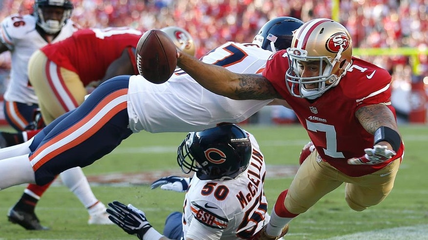 San Francisco 49ers quarterback Colin Kaepernick (7) is pushed out of bounds by Chicago Bears free safety Chris Conte, top, as Shea McClellin helps on defense during the first quarter of an NFL football game in Santa Clara, Calif., Sunday, Sept. 14, 2014. (AP Photo/Tony Avelar)
