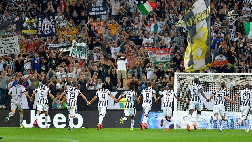 Juventus players celebrate their 2-0 win over Udinese at the end of a Serie A soccer match at the Juventus stadium, in Turin, Italy, Saturday, Sept. 13, 2014. Juventus continued to show little has changed since Massimiliano Allegri took charge as it eased to a 2-0 win against Udinese on Saturday in the former AC Milan coach's home debut. (AP Photo/Massimo Pinca)