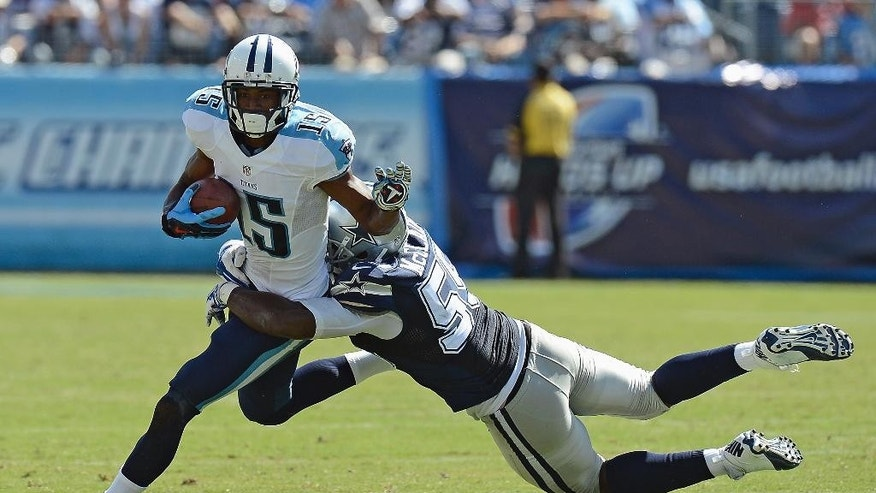 Tennessee Titans wide receiver Justin Hunter (15) is brought down by Dallas Cowboys linebacker Rolando McClain (55) in the fourth quarter of an NFL football game Sunday, Sept. 14, 2014, in Nashville, Tenn. (AP Photo/Mark Zaleski)