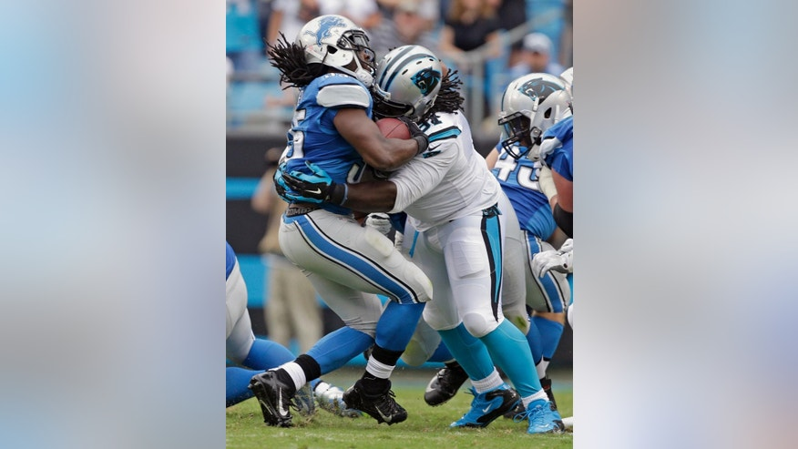 Detroit Lions' Joique Bell (35) is stopped by Carolina Panthers' Colin Cole (91) during the first half of an NFL football game in Charlotte, N.C., Sunday, Sept. 14, 2014. (AP Photo/Bob Leverone)