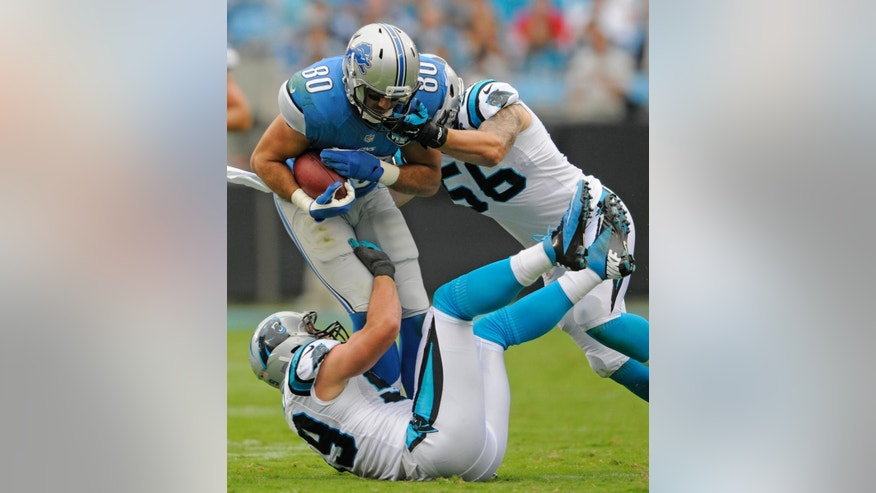 Detroit Lions' Joseph Fauria (80) is tackled by Carolina Panthers' A.J. Klein (56) and Luke Kuechly (59) during the first half of an NFL football game in Charlotte, N.C., Sunday, Sept. 14, 2014. (AP Photo/Mike McCarn)