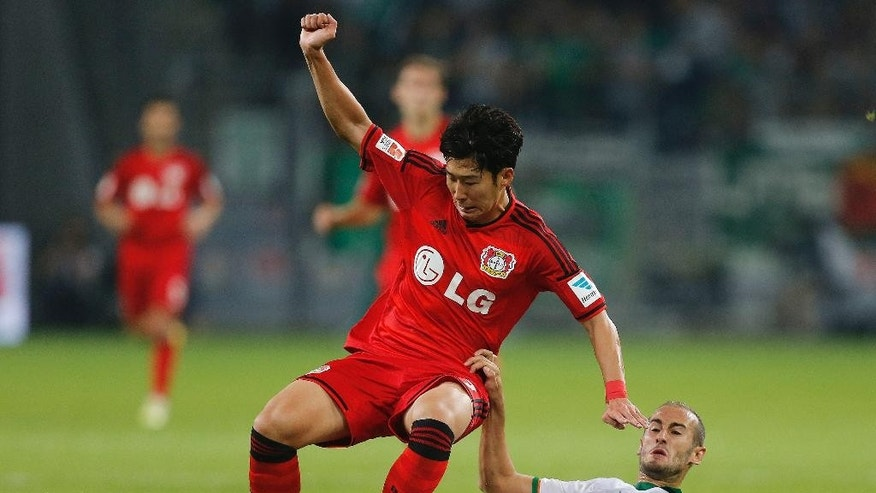 Leverkusen's Son Heung-min from South Korea, left, and Bremen's Alejandro Galvez from Spain challenge for the ball during the German first division Bundesliga soccer match between Bayer Leverkusen and Werder Bremen in Leverkusen, Germany, Friday, Sept. 12, 2014. (AP Photo/Frank Augstein)