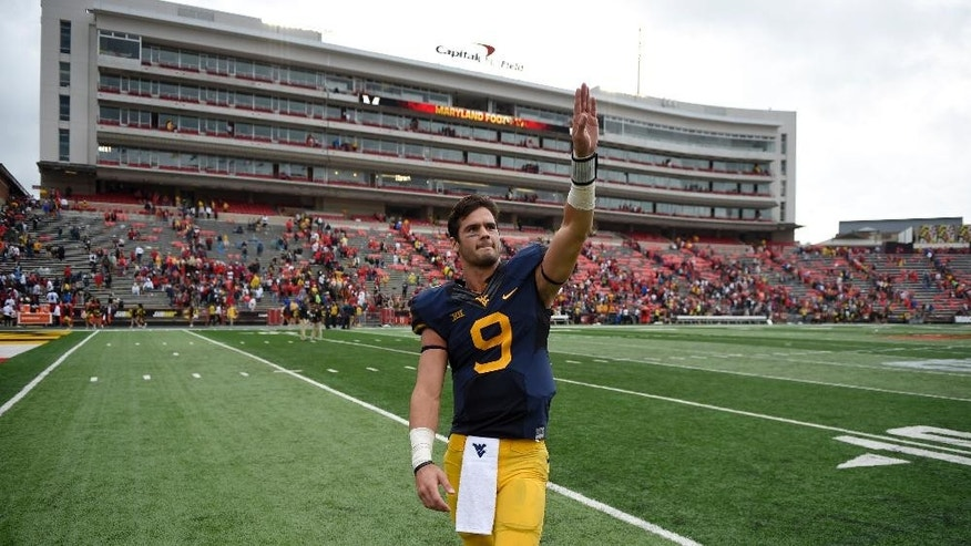 West Virginia quarterback Clint Trickett (9) waves to the crowd after they defeated Maryland 40-37 in an NCAA college football game, Saturday, Sept. 13, 2014, in College Park, Md. (AP Photo/Nick Wass)