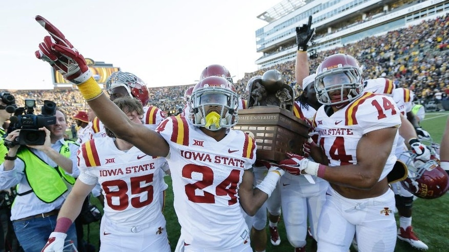 Iowa State players celebrate with the Cy-Hawk trophy after defeating Iowa 20-17 in an NCAA college football game, Saturday, Sept. 13, 2014, in Iowa City, Iowa. (AP Photo/Charlie Neibergall)