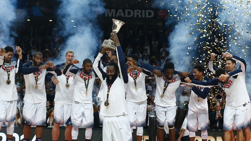 United States' James Harden lifts the trophy alongside the rest of the team players as they celebrate wining the final of the World Cup Basketball match between the United States and Serbia at the Palacio de los Deportes stadium in Madrid, Spain, Sunday, Sept. 14, 2014. (AP Photo/Andres Kudacki)
