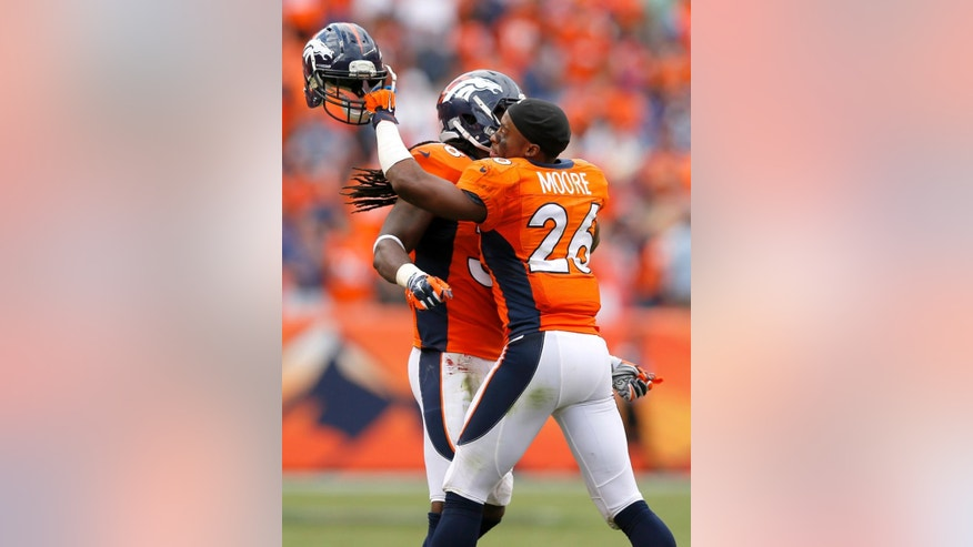 Denver Broncos free safety Rahim Moore (26) embraces teammate Quinton Carter during the final seconds during the second half of an NFL football game against the Kansas City Chiefs , Sunday, Sept. 14, 2014, in Denver. The Broncos won 24-17. (AP Photo/Jack Dempsey)
