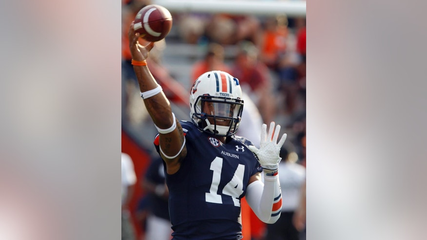 FILE - In this Sept. 6, 2014, file photo, Auburn quarterback Nick Marshall (14) warms up before an NCAA college football game against San Jose State in Auburn, Ala. Marshall thought about going to Kansas State. When he didn't, Jake Waters did. Now, the two quarterbacks shared the spotlight Thursday night when Marshall leads No. 5 Auburn against Waters and No. 20 Kansas State.  (AP Photo/Butch Dill, File0