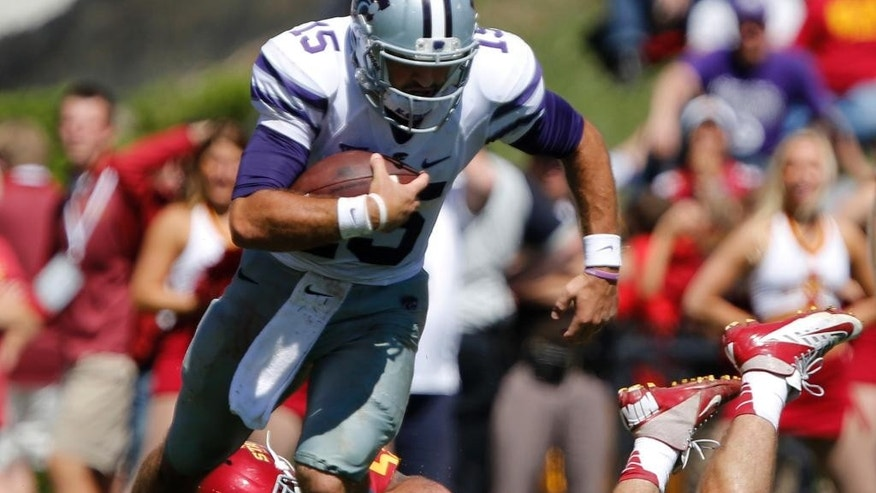 FILE - In this Sept. 6, 2014, file photo, Kansas State quarterback Jake Waters (15) breaks away from the grasp of Iowa State linebacker Jevohn Miller (55) during the second half of an NCAA college football game in Ames, Iowa. Nick Marshall thought about going to Kansas State. When he didn't, Jake Waters did. Now, the two quarterbacks shared the spotlight Thursday night when Marshall leads No. 5 Auburn against Waters and No. 20 Kansas State.  (AP Photo/Justin Hayworth, File)