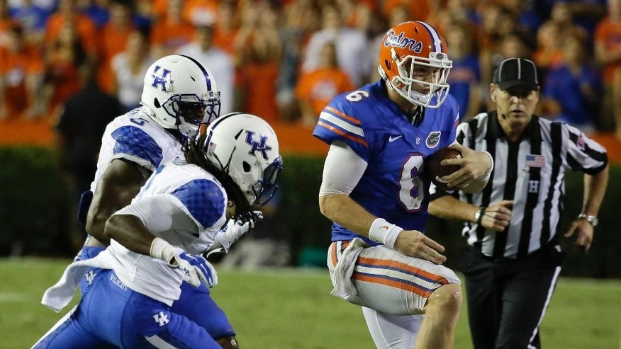 Florida quarterback Jeff Driskel (6) is run out of bounds by Kentucky defensive end Jason Hatcher, left rear, and cornerback Fred Tiller as he scrambles out of the pocket during the second half of an NCAA college football game in Gainesville, Fla., Saturday, Sept. 13, 2014. (AP Photo/John Raoux)