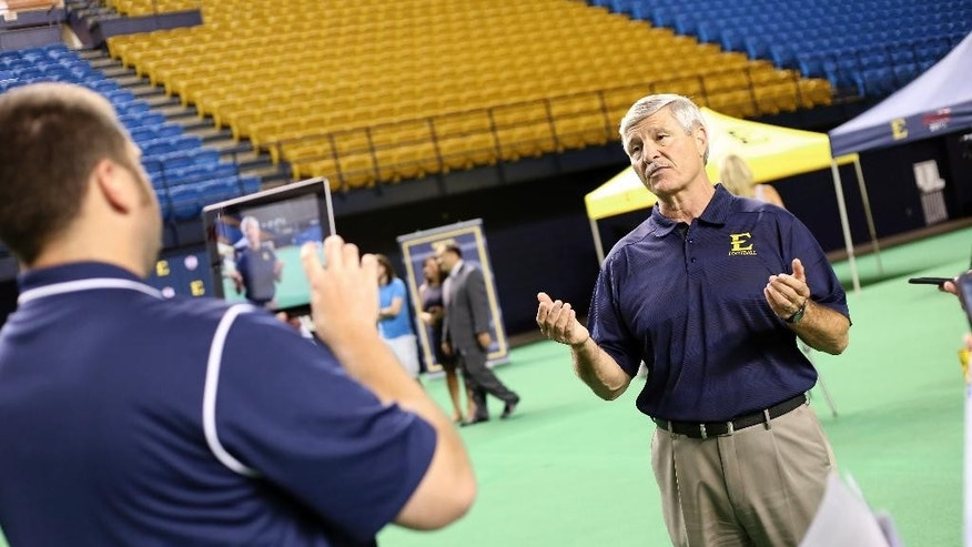 In this Sept. 3, 2014 photo, East Tennessee State head coach Carl Torbush talks to the media during the school's NCAA college football media day in Johnson City, Tenn. Longtime friends and former Atlantic Coast Conference rivals Torbush and Mike O'Cain say they savor the opportunity to work together in relaunching a program on a smaller scale at East Tennessee State. They spent a lot of the 1990s trying to beat the other while both were in North Carolina. (AP Photo/East Tennessee State, Ron Campbell)